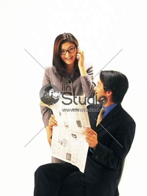 Young casual couple on the phone, man reading newspaper, upset woman on mobile phone