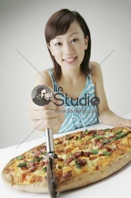 Beautiful girl cut pizza