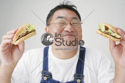 Mid Adult Man Eating  Hamburgers