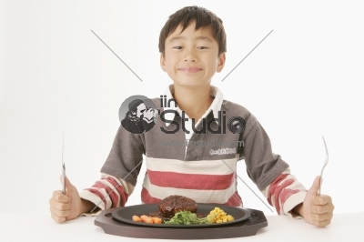 Young Boy Eating a Hamburger Steak