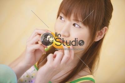 Beautiful young woman eating segments of an orange