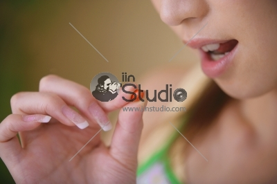 Young woman taking the pill - Focus is on a pill