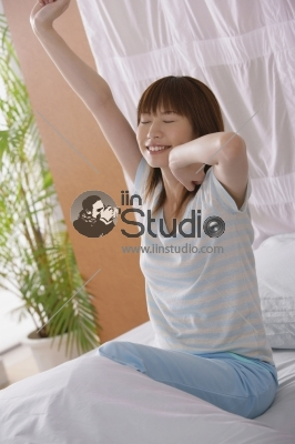 Woman stretching on side of bed