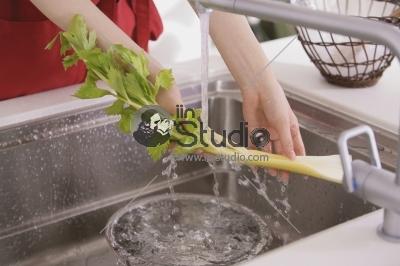 Young Woman Washing Celery