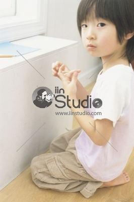 A Young Boy drawing on the color paper