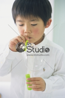 A Young Boy blowing soap bubbles
