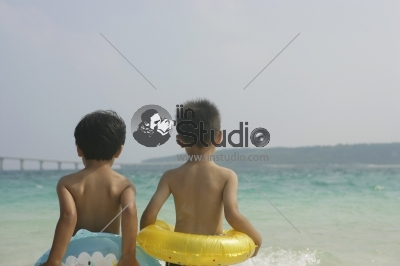 Young boys standing at the beach, rear view