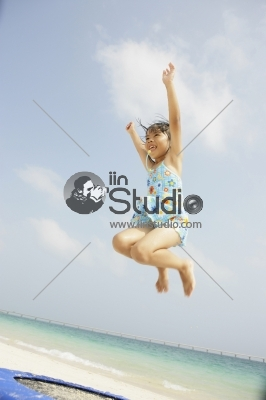 Young girl jumping on trampoline at the beach