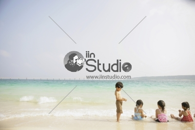 Young girls sitting and one young boy standing at the beach