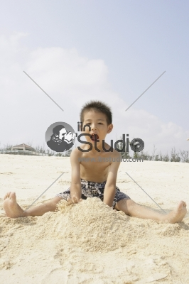 Young boy playing in sand on beach