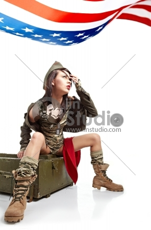 Young attractive girl dressed in old battle coat sitting, Vintage style studio shot