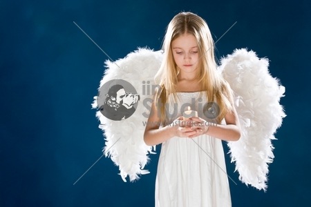 Portrait of peaceful girl wearing white wings looking at candle in her hands over blue background