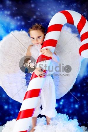 Beautiful little angelic child with a huge candy at a christmas background.