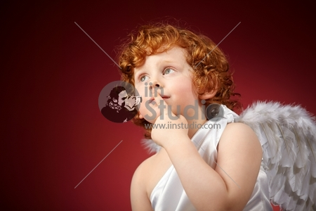 Portrait of the small thoughtful boy with wings behind the back on a red background