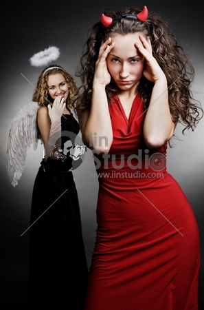 angel and devil over dark background