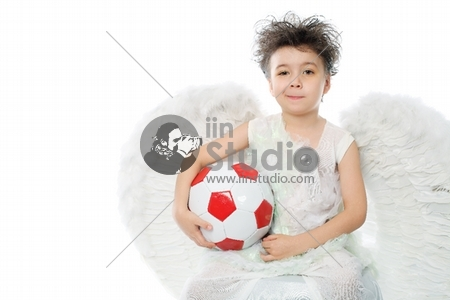 Beautiful little angel holding a ball. Isolated over white