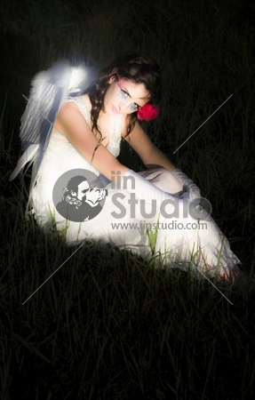 Magical And Glowing Enchanted Angel Resting On A Grassy Meadow At Night With Her Wings Illuminating The Dark Scene In A Supernatural And Mystical Concept