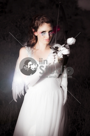 Cupid The Beautiful Goddess Of Love Standing In All White Attire With Wing While Holding A Bow And Rose Arrow Ready To Set Alight The Passion Of Love