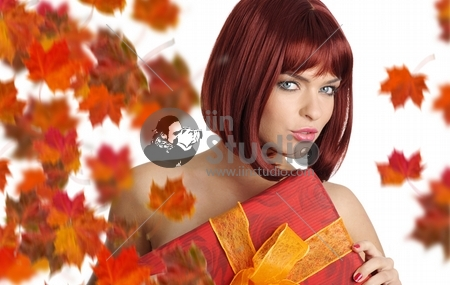 Autumn girl smiles and holding a gift in packing