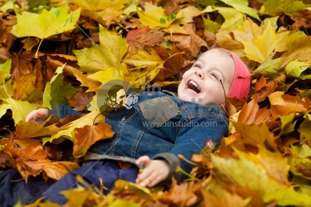 a little child playing in the leaves