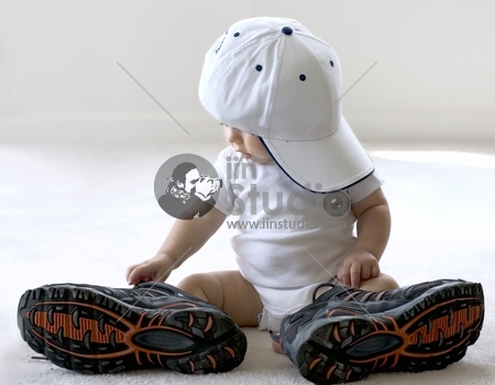 Adorable baby trying on shoes that are way too big for him