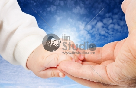 Baby holding fathers hand against blue sky background