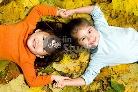 Two young girls playing in the Autumn Leaves