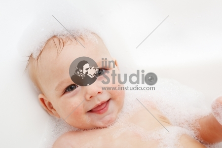 Adorable bath baby boy with soap suds on hair