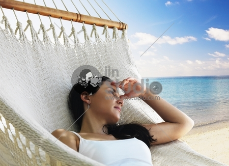 Beautiful woman lying in hammock near the ocean