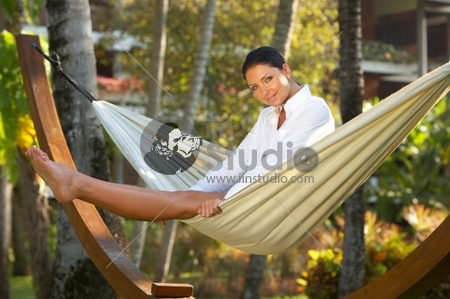 20-25 years woman portrait relaxing on hammock at exotic surrounding