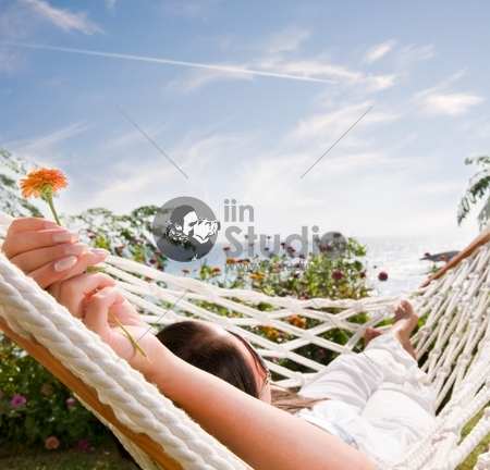 Young woman in hammock, focus on the flower (shallow dof)
