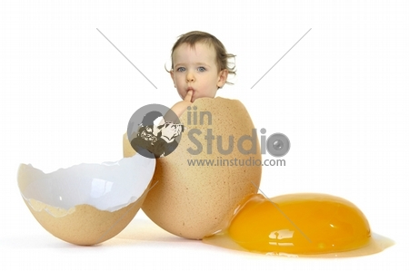 Beautiful baby inside an egg isolated in white