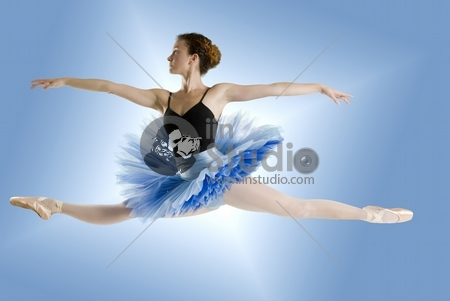 Dancer in blue tutu jumpig on a shining blue background