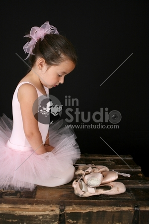 Beautiful brunette girl wearing a pink tutu sitting by pointe shoes