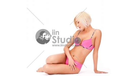 beautiful blond woman wearing pink lingerie over white