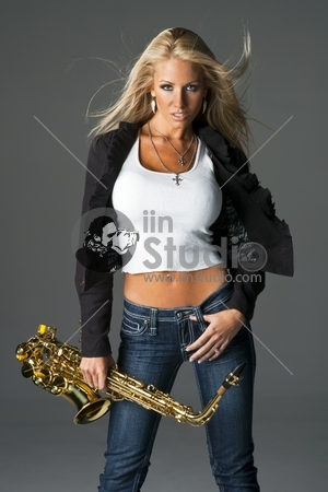 A blonde model holding a saxaphone in a studio environment