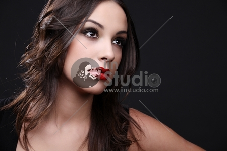 Young attractive woman posing in black dress. Studio shoot.
