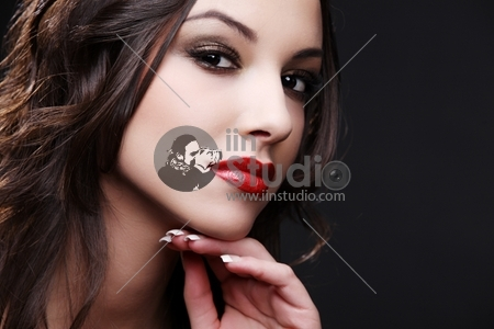 Portrait of beautiful young woman on black background.