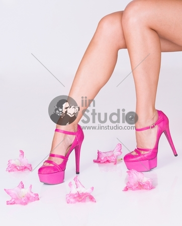 Woman in fashion pink high heels surrounded with flowers