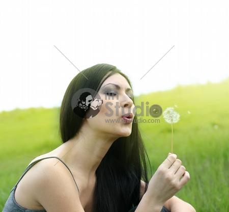 beautiful woman blowing dandelion on the meadow