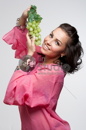 Beautiful woman holding green grape in her hands