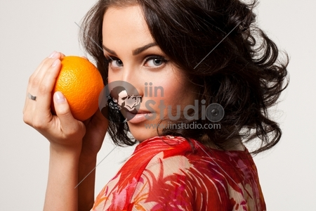 Picture of a beautiful young woman holding orange in hands