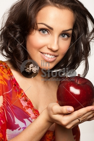 Picture of a happy beautiful woman holding big red apple in hands