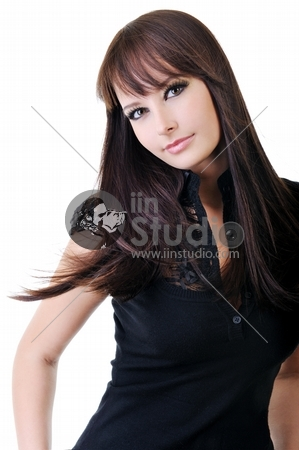 Beautiful young adult girl in black elegant dress posing in studio