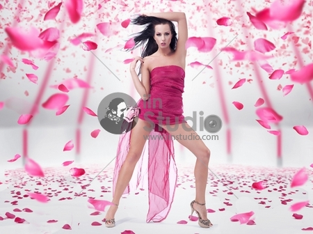 Young woman posing over rose petals background