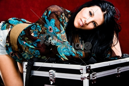 young woman leaned on big suitcase, studio shot