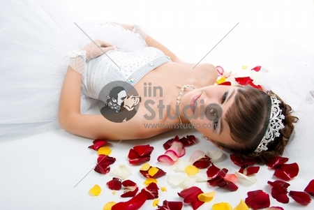 Beautiful sexy bride on floor among red rose petals on white background