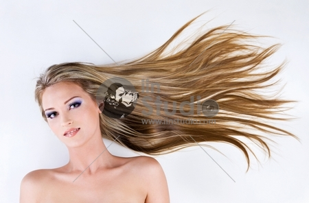 beautiful young female face with long blond straight hair as background