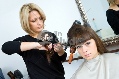 hair stylist and woman with brushes in her hair in hair salon