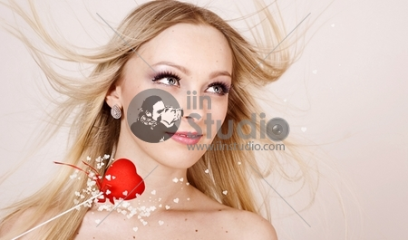 Portrait Of A Lovely Young Girl Holding A Red Heart Over White Background